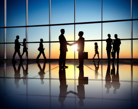 Business people walk and meet in a large corridor of an office building.  The scene is against a sunny sky behind a large office window.  The people appear as silhouettes and are reflected off of the surface of the floor.